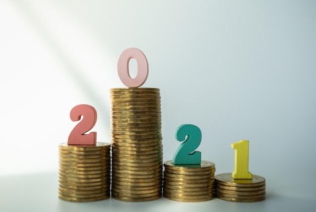 2021 pieniądze, biznes i koncepcja planowania. kolorowy drewniany numer stos list złotych monet.