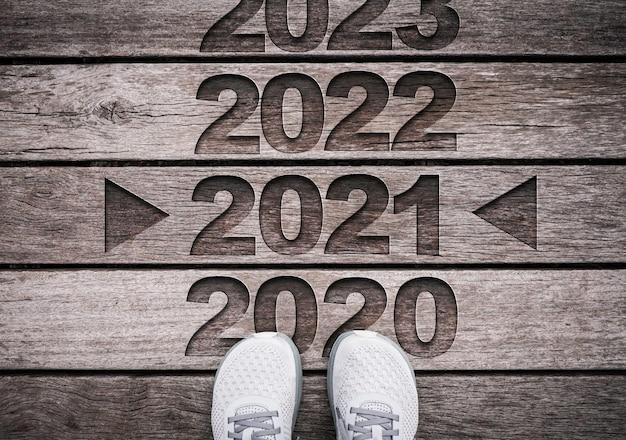2021 rok wyrzeźbiony na starym drewnie z butami.