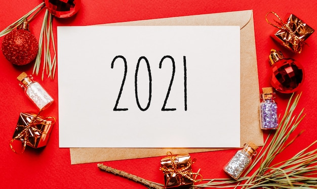 2021 świąteczna notatka z prezentem, gałązką jodły i zabawką na czerwono