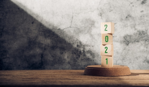 2021 szczęśliwego nowego roku na drewnianym bloku na drewnianym stole i betonowej ścianie z światłem słonecznym z okna