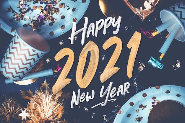 2021 szczęśliwego nowego roku pociągnięcie pędzlem na marmurowym stole z kubkiem imprezowym, dmuchawą imprezową, świecidełkiem, konfetti