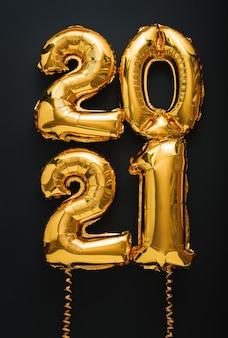 2021 szczęśliwego nowego roku złote balony z tekstem wstążkami na czarnym formacie pionowym.