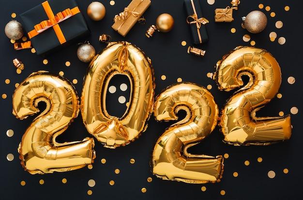2022 balon złoty tekst na czarnym tle ze złotym konfetti, pudełka na prezenty świąteczne, złote kulki, świąteczny wystrój. szczęśliwego nowego roku zaproszenie z bożonarodzeniowymi złotymi balonami foliowymi 2022.