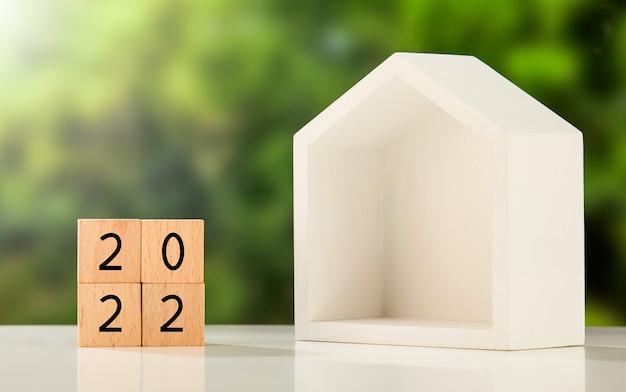 """""""2022"""" napisane na drewnianych kostkach i domek na stole"""