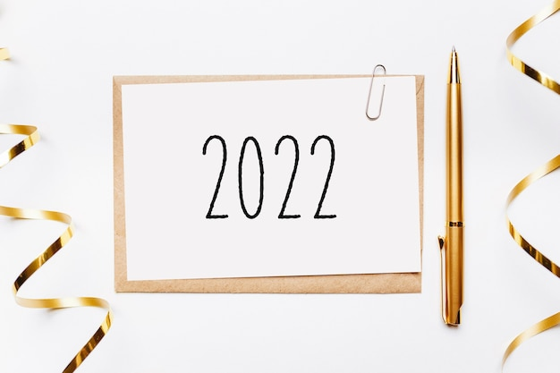 2022 notatka z kopertą, prezentami i złotą wstążką na białym tle