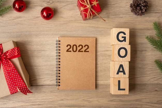 2022 nowy rok z notatnikiem, prezentem na boże narodzenie i długopisem na drewnianym stole. boże narodzenie, szczęśliwego nowego roku, cele, postanowienie, lista rzeczy do zrobienia, start, strategia i koncepcja planu