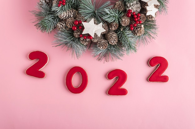 2022 nowy rok z piernika i bożonarodzeniowego wieńca na różowym tle. szczęśliwego nowego roku 2022.