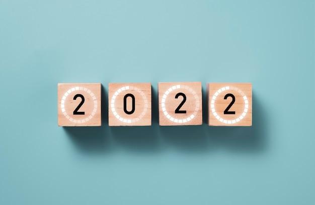 2022 rok ze znakiem ładowania na drewnianym bloku kostki z niebieskim tłem, koncepcją przygotowania wesołych świąt i szczęśliwego nowego roku.