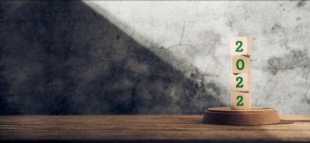 2022 szczęśliwego nowego roku na drewnianym bloku na drewnianym stole i betonowej ścianie ze światłem słonecznym z okna. nadzieję na koncepcję nowego roku