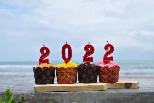 2022 szczęśliwego nowego roku z babeczkami i świeczkami na plaży