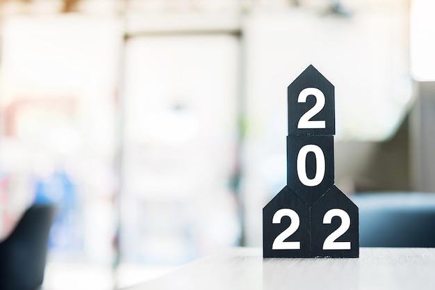 2022 szczęśliwego nowego roku z drewnianym modelem domu na stole biurowym. koncepcje nowych domów, ubezpieczeń finansowych, majątkowych i nieruchomości