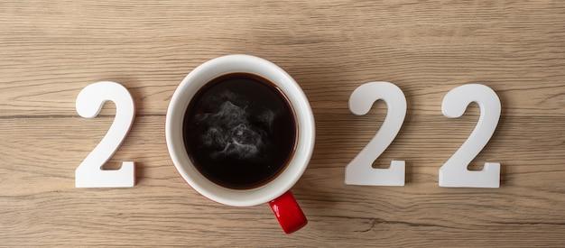 2022 szczęśliwego nowego roku z filiżanką kawy i świąteczną dekoracją na tle stołu z drewna. nowy start, rozwiązanie, odliczanie, cele, plan, działanie i koncepcja misji