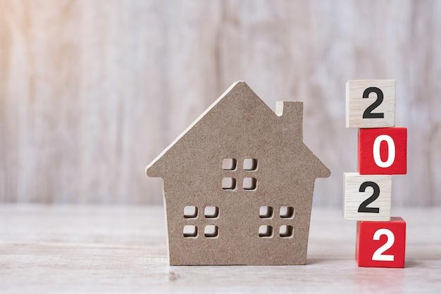 2022 szczęśliwego nowego roku z modelem domu na drewnianym tle stołu. koncepcje bankowe, nieruchomościowe, inwestycyjne, finansowe, oszczędnościowe i noworoczne