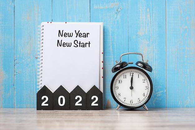 2022 szczęśliwego nowego roku z nowym rokiem nowy początek, czarny retro budzik i drewniany numer. koncepcja rozwiązania, celów, planu, działania i misji