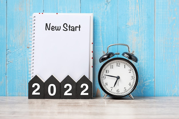 2022 szczęśliwego nowego roku z nowym startem, czarnym retro budzikiem i drewnianym numerem. koncepcja rozwiązania, celów, planu, działania i misji