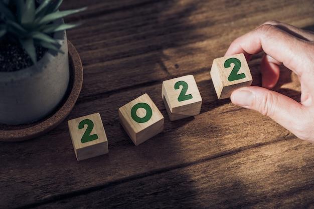 2022 szczęśliwego nowego roku z ręką podnieś drewniany blok na drewnianym stole ze światłem słonecznym z okna. mam nadzieję na koncepcję nowego roku