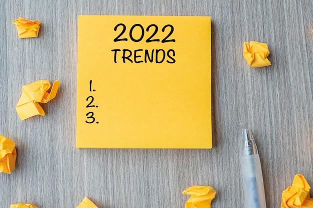 2022 trendy słowo na żółtą notatkę z piórem i pokruszonym papierem na tle drewnianego stołu. nowy rok nowy start, postanowienia, strategia i koncepcja celu