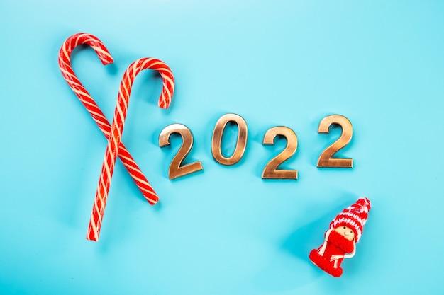 2022 złote figurki, cyfry, laska cukrowa i gnom lub szwedzki tomte, na niebieskim tle. obchody szczęśliwego nowego roku. złote cyfry, tło wakacje, pocztówka, impreza. błyszczące liczby, miejsce na kopię