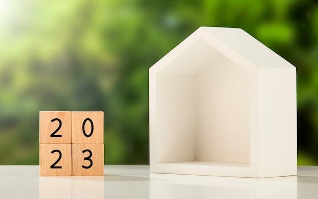 """""""2023"""" napisane na drewnianych kostkach i domek na stole"""