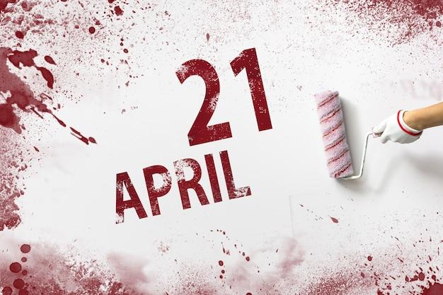 21 kwietnia. 21 dzień miesiąca, data kalendarzowa. ręka trzyma wałek z czerwoną farbą i pisze datę w kalendarzu na białym tle. miesiąc wiosny, koncepcja dnia roku.