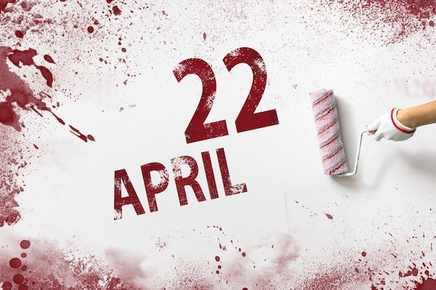 22 kwietnia. 22 dzień miesiąca, data kalendarzowa. ręka trzyma wałek z czerwoną farbą i pisze datę w kalendarzu na białym tle. miesiąc wiosny, koncepcja dnia roku.