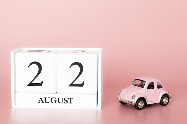 22 sierpnia, dzień 22 miesiąca, kostka kalendarza na nowoczesnym różowym tle z samochodem