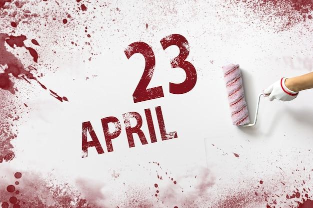 23 kwietnia. 23 dzień miesiąca, data kalendarzowa. ręka trzyma wałek z czerwoną farbą i pisze datę w kalendarzu na białym tle. miesiąc wiosny, koncepcja dnia roku.