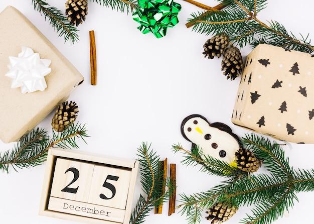 25 grudnia napis na drewnianych klockach z zielonymi gałązkami