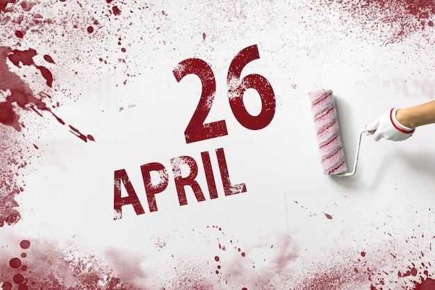 26 kwietnia. 26 dzień miesiąca, data kalendarzowa. ręka trzyma wałek z czerwoną farbą i pisze datę w kalendarzu na białym tle. miesiąc wiosny, koncepcja dnia roku.