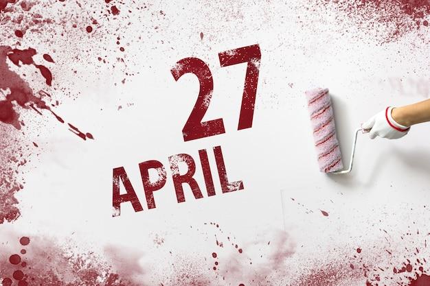 27 kwietnia. 27 dzień miesiąca, data kalendarzowa. ręka trzyma wałek z czerwoną farbą i pisze datę w kalendarzu na białym tle. miesiąc wiosny, koncepcja dnia roku.