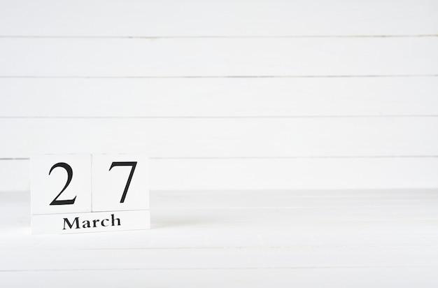 27 marca, dzień 27 miesiąca, urodziny, rocznica, drewniany kalendarz blokowy na białym drewnianym tle z kopią miejsca na tekst.