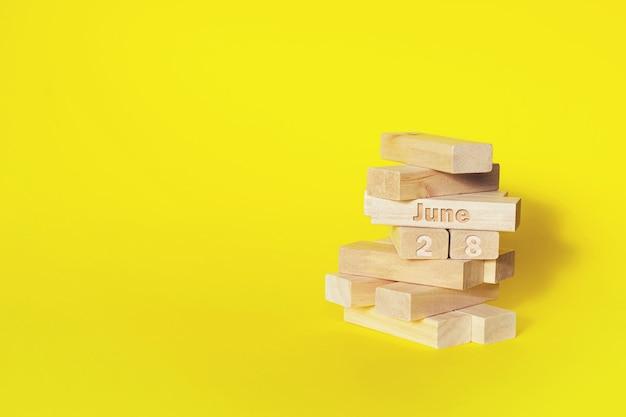 28 czerwca. 28 dzień miesiąca, data kalendarzowa. drewniane klocki składane w wieżę za miesiąc