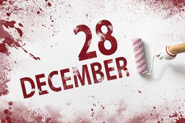 28 grudnia. 28 dzień miesiąca, data kalendarzowa. ręka trzyma wałek z czerwoną farbą i pisze datę w kalendarzu na białym tle. miesiąc zimowy, koncepcja dnia roku.