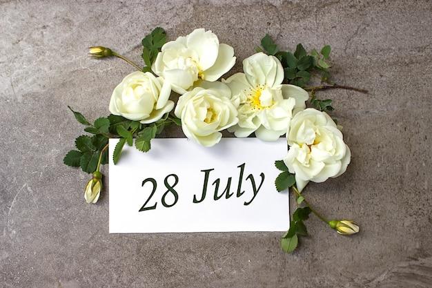 28 lipca. 28 dzień miesiąca, data kalendarzowa. białe róże obramowania na pastelowym szarym tle z datą kalendarzową. miesiąc letni, koncepcja dnia roku.