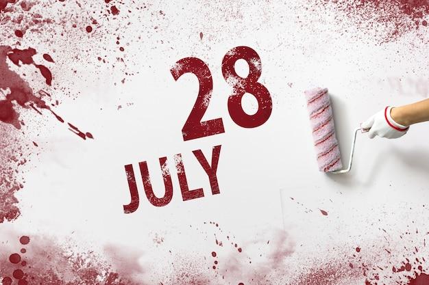 28 lipca. 28 dzień miesiąca, data kalendarzowa. ręka trzyma wałek z czerwoną farbą i pisze datę w kalendarzu na białym tle. miesiąc letni, koncepcja dnia roku.