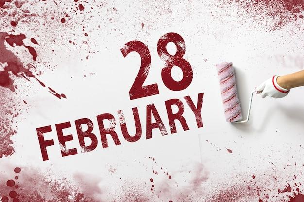 28 lutego. 28 dzień miesiąca, data kalendarzowa. ręka trzyma wałek z czerwoną farbą i pisze datę w kalendarzu na białym tle. miesiąc zimowy, koncepcja dnia roku.