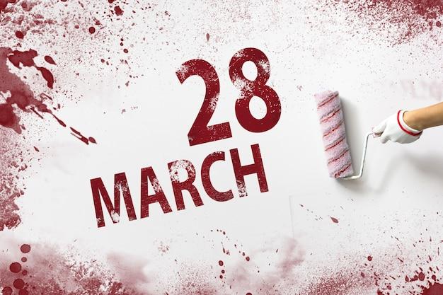 28 marca. 28 dzień miesiąca, data kalendarzowa. ręka trzyma wałek z czerwoną farbą i pisze datę w kalendarzu na białym tle. miesiąc wiosny, koncepcja dnia roku.