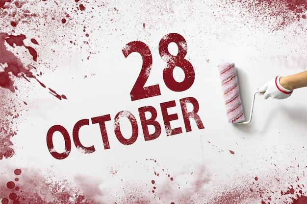 28 października. 28 dzień miesiąca, data kalendarzowa. ręka trzyma wałek z czerwoną farbą i pisze datę w kalendarzu na białym tle. jesienny miesiąc, koncepcja dnia roku.