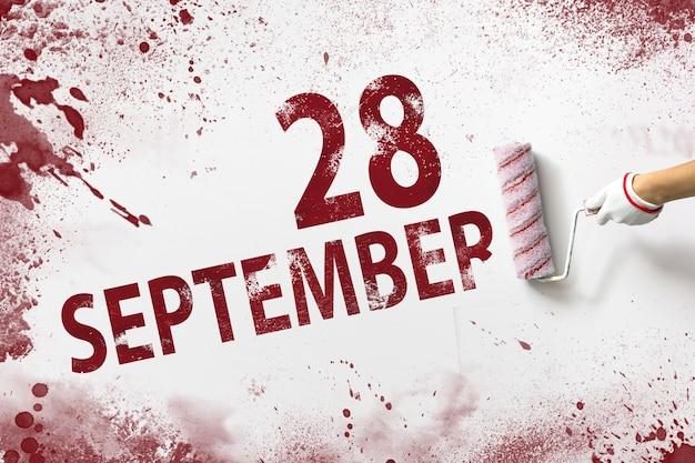 28 września. 28 dzień miesiąca, data kalendarzowa. ręka trzyma wałek z czerwoną farbą i pisze datę w kalendarzu na białym tle. jesienny miesiąc, koncepcja dnia roku.
