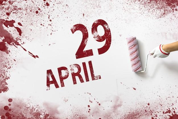 29 kwietnia. 29 dzień miesiąca, data kalendarzowa. ręka trzyma wałek z czerwoną farbą i pisze datę w kalendarzu na białym tle. miesiąc wiosny, koncepcja dnia roku.
