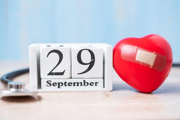 29 września biały kalendarz i stetoskop w kształcie czerwonego serca