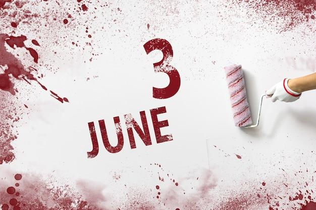 3 czerwca. dzień 3 miesiąca, data kalendarzowa. ręka trzyma wałek z czerwoną farbą i pisze datę w kalendarzu na białym tle. miesiąc letni, koncepcja dnia roku.