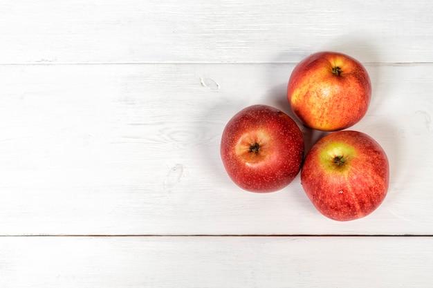 3 dojrzałe czerwone jabłka na białym drewnianym stole