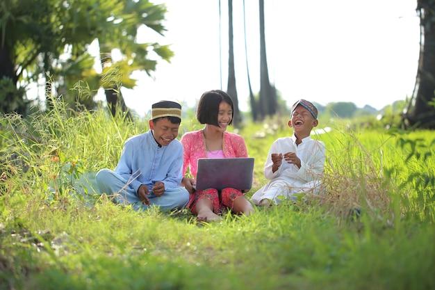 3 dzieci w muzułmańskich ubraniach siedzą i oglądają internet na laptopie dla zabawy w ogrodzie rolnym.