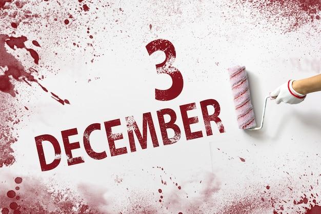 3 grudnia. dzień 3 miesiąca, data kalendarzowa. ręka trzyma wałek z czerwoną farbą i pisze datę w kalendarzu na białym tle. miesiąc zimowy, koncepcja dnia roku.
