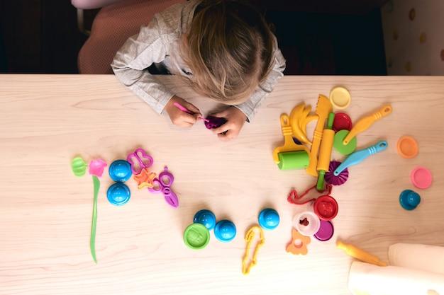 3 Lata Dziewczyna Sztuki Twórczej. Ręce Dziecka Bawiące Się Kolorową Glinianą Plasteliną. Samoizolacja Covid-19, Edukacja Online, Nauczanie W Domu. Maluch Dziewczyna Uczy Się W Domu, Nauka W Domu Premium Zdjęcia
