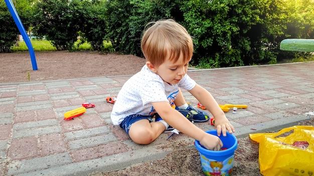 3-letni chłopiec w koszulce i spodenkach siedzi na ziemi na placu zabaw i bawi się mnóstwem kolorowych zabawek