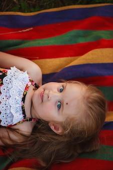 3 letnia dziewczynka leży na kolorowej narzucie