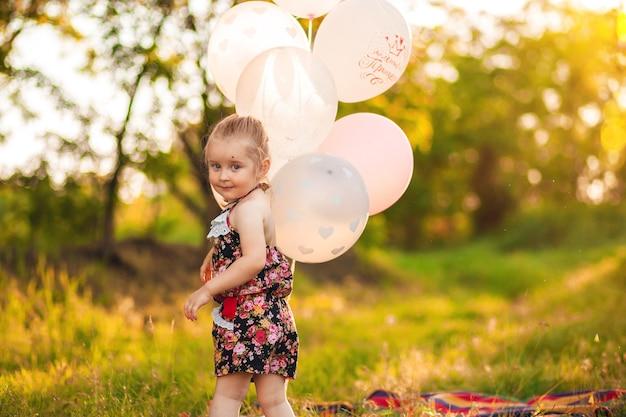 3-letnia gil bawi się biało-różowymi balonikami w letnim ogródku