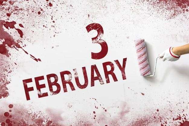 3 lutego. dzień 3 miesiąca, data kalendarzowa. ręka trzyma wałek z czerwoną farbą i pisze datę w kalendarzu na białym tle. miesiąc zimowy, koncepcja dnia roku.